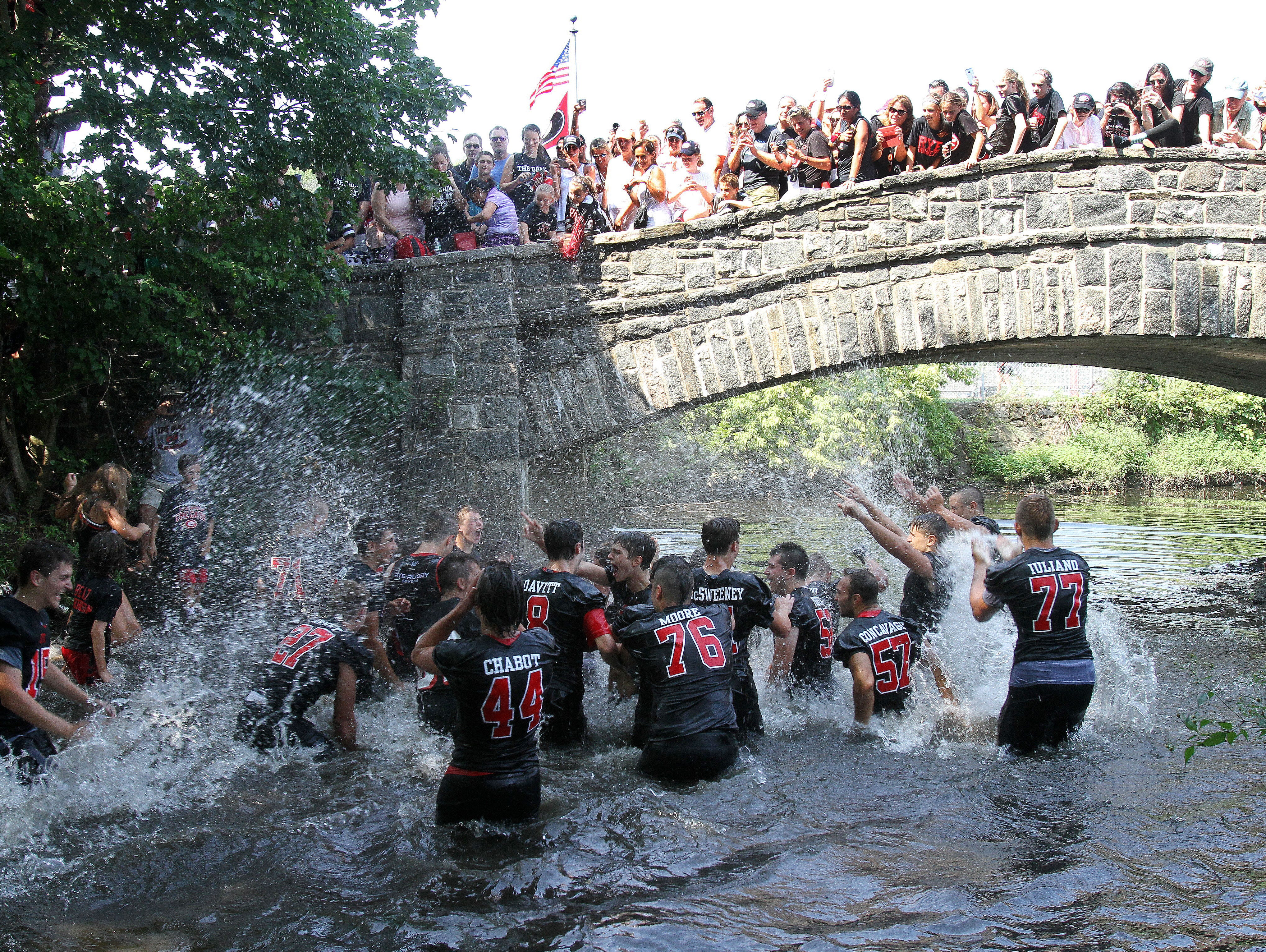 Rye players jump into the creek alongside the field as they celebrate their 42-12 victory over Harrison in the annual rivalry game at Nugent Stadium at Rye High School Sept. 10, 2016.