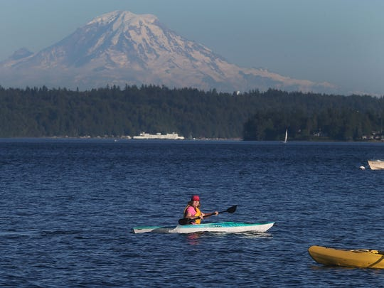 Mount Rainier looms in the distance as kayakers paddle