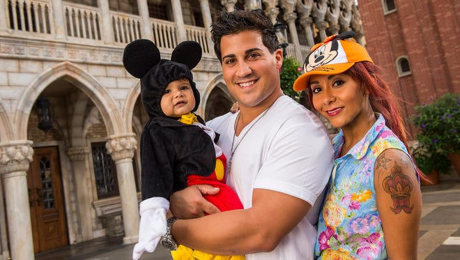 """Nicole """"Snooki"""" Polizzi, fiance Jionni LaValle and their  son, Lorenzo, 1,  pose inside the Italy pavilion in the Epcot theme park on Sept. 27, 2013, at Walt Disney World in Florida."""