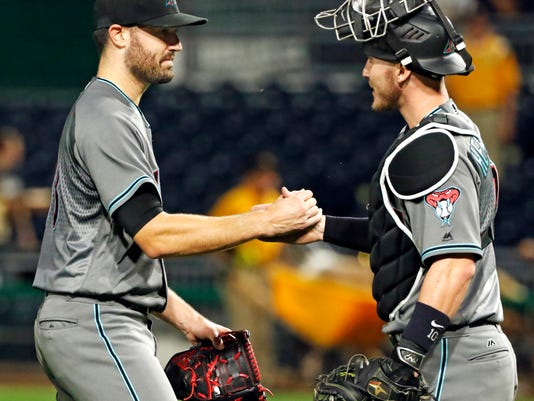 Arizona Diamondbacks starting pitcher Robbie Ray, left, celebrates with catcher Chris Herrmann after a baseball game against the Pittsburgh Pirates in Pittsburgh, Tuesday, May 30, 2017. Ray pitched a complete game, four-hit, 3-0 shutout. (AP Photo/Gene J. Puskar)