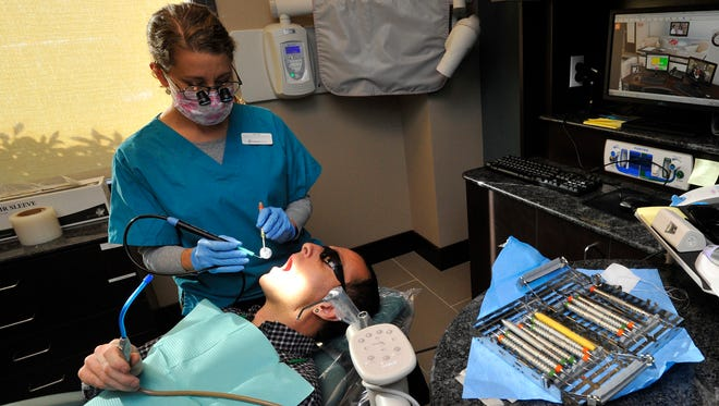 In this photo taken Wednesday, Oct. 21, 2015, Nicole Olts, a dental hygienist at PureCare Dental in Bend, Ore., works on cleaning the teeth of Dave Beach. More dentists are marketing memberships plans, in which patients pay a set annual or monthly fee, which typically covers preventive care and entitles them to discounts on other work, such as fillings and crowns . At least three independent practices in Central Oregon offer membership plans, as does PureCare Dental, with a range of discounts. (Ryan Brennecke/The Bulletin via AP) MANDATORY CREDIT