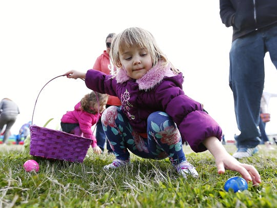 Izzy Smith, 5, picks up eggs laying in the grass during