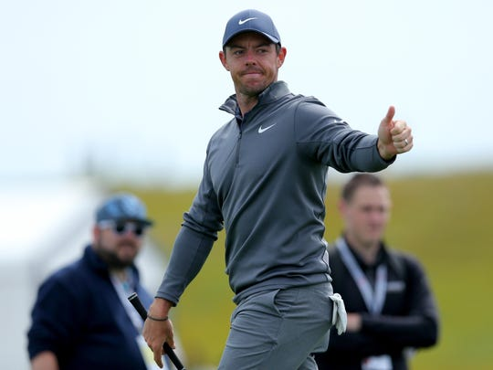 Rory McIlroy acknowledges fans after hitting from the