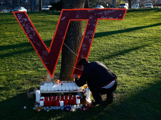 Virginia Tech student Daniel Hamilton writes on a memorial constructed on the Virginia Tech campus for the victims of yesterday's mass killings April 17, 2007 in Blacksburg, VA. Memorial services for those killed in the school shooting are expected to be held later today.