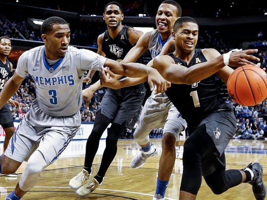 University of Memphis teammates Jeremiah Martin (left) and Jimario Rivers (middle) battle University of Central Florida guard B.J. Taylor  (right) for a rebound as A.J. Davis (middle back) looks on during first half action at the FedExForum.