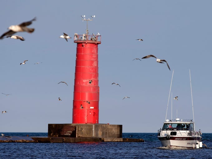 Seagulls fly near a charter boat by the lighthouse