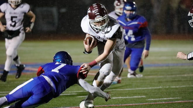 Killingly's Jack Sharpe looks to avoid a tackle from Waterford's Christian Hightower during last year's Class M semifinal at Waterford High School.