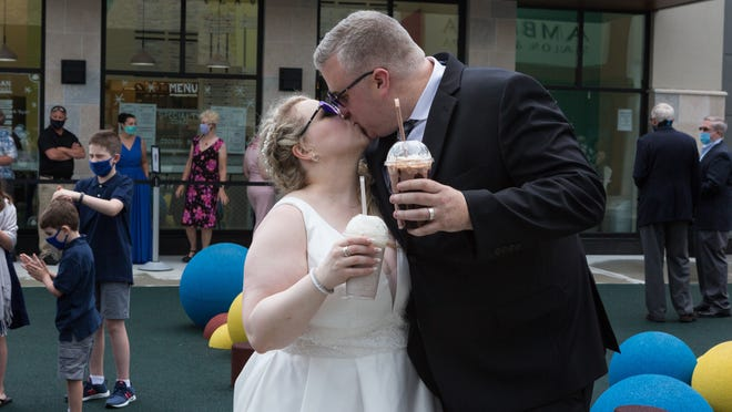 Jessica Kennedy, left and Greg Kennedy, from Hanover, kiss as newlyweds with ice cream frappes in their hands during the wedding reception on Friday June 26, 2020, at Lil Duke's Ice Cream shop in Hanover. Lauren Owens Lambert/For The Patriot Ledger