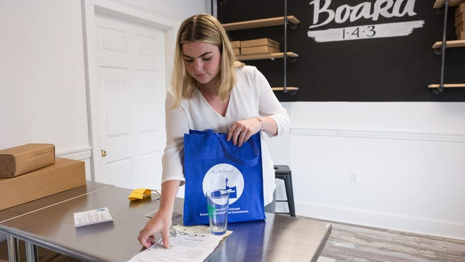 Emily Shea, Social Media Intern with Scituate Loves Local, packs a bag full of local goods and gift cards as part of the Scituate Loves Local boxes for residents to promote local business during COVID-19 at Board 143 in Scituate. Photo by Lauren Owens Lambert / for The Patriot Ledger.