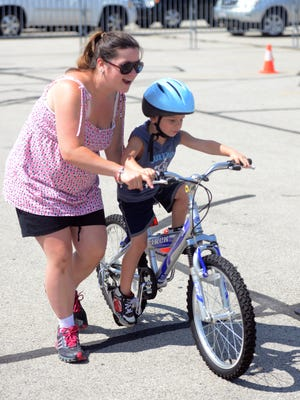 Sara Process works with John Process, Jr., on the bike rodeo course in the Lambeau Field parking lot.