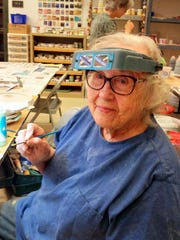 Peggy Alford takes a break while painting her sculpted