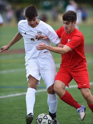From left, Arlington's Michael Vanikiotis and Roy C. Ketcham's Mitchell Kuehner battle for the ball during Wednesday's game at Arlington High School.