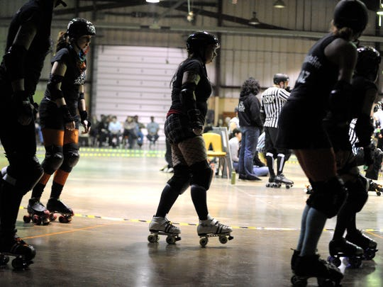 """Mike Tripp/The News Leader The members of the black team cruise around the track during skater introductions before the """"mix up"""" scrimmage where players from both the Charlottesville Derby Dames and Richmond Derby Demons were mixed together to form two opposing squads. The event featured women's flat track roller derby scrimmages held at Augusta Expo in Fishersville on Sunday, March 7, 2010."""