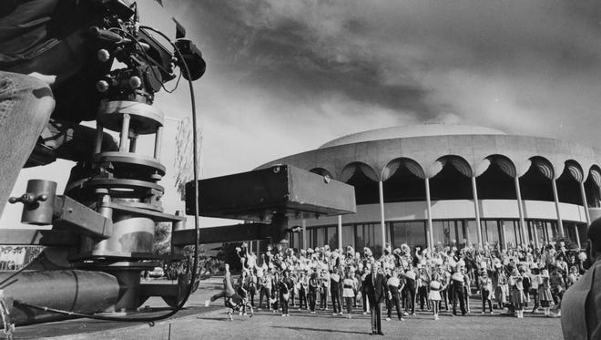 Former ASU President J. Russell Nelson stands in front of Gammage Center for the Performing Arts in 1986 with ASU cheerleaders and band members to tape a promotional spot for the Rose Bowl.