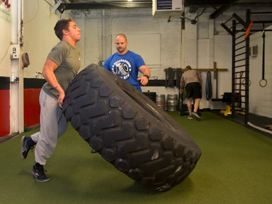 Zach Even-Esh, owner of the Underground Strength Gym in Manasquan NJ watches as Giancarlo Crivelli, 17, of Point Pleasant Beach does tire flips on October 1, 2015 where he trains athletes young and old. Zach is holding a fundraiser for the Navy Seals Foundation among other philanthropies.