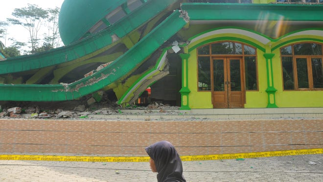 A Muslim woman walks past a mosque that collapsed after a 6.1-magnitude quake rocked Java island, in Banyumas, Indonesia.