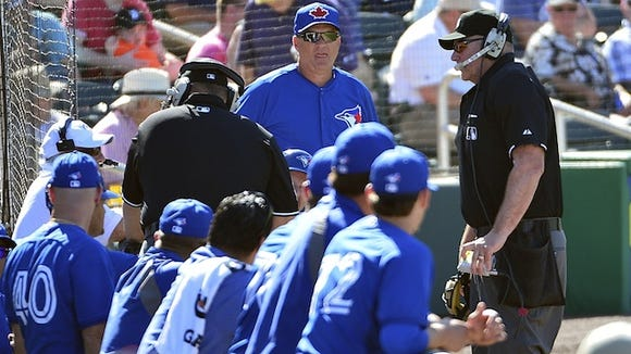 Umpires speak to the replay official after the Toronto Blue Jays manager John Gibbons challenges a play call at first base during on Monday.