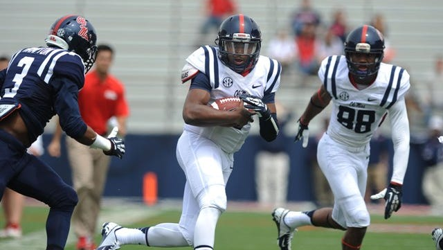 Ole Miss quarterback DeVante Kincade keeps for yardage during Saturday's Grove Bowl.