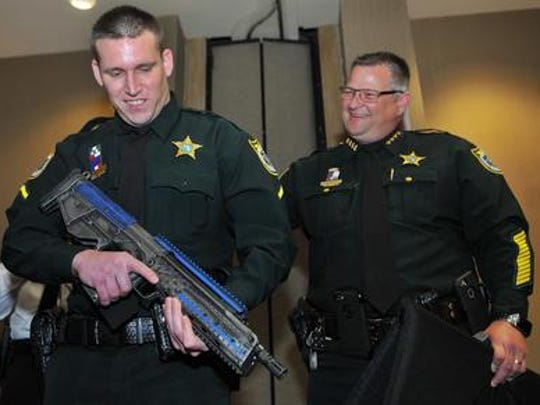 Deputy Nicholas Worthy and Sheriff Wayne Ivey of the Brevard County Sheriff's Office admire the Kel-Tec RDB rifle awarded to Worthy as Officer of the Year.