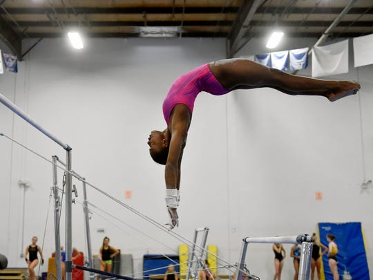 Trinity Thomas practices her uneven bars routine Thursday,