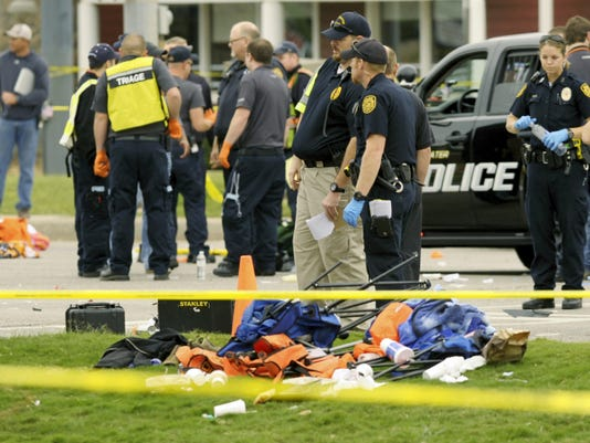 Police investigators look over the scene after a vehicle crashed into a crowd of spectators during the Oklahoma State University homecoming parade, causing multiple injuries, on Saturday, Oct. 24, 2015 in Stillwater, Oka.(AP Photo/Brody Schmidt)