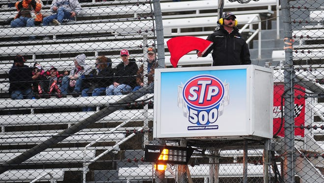 A NASCAR official waves a red flag during practice for the NASCAR Camping World Truck Series Kroger 250 at Martinsville Speedway on March 28, 2014 in Martinsville, Va.