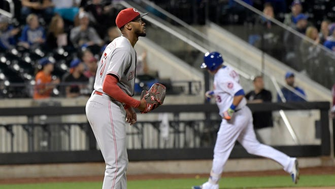 Cincinnati Reds pitcher Amir Garrett, left, reacts as New York Mets' Travis Taijeron, right, rounds the bases with a home run during the second inning.