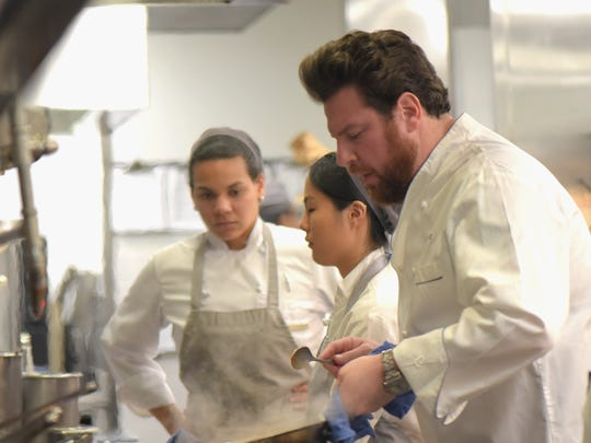 Chef Scott Conant prepares food for a dinner during
