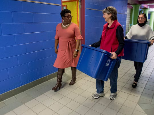 School counselor Karen Wilson, left, walks with Nelya McKenzie, center, and Nancy Jo Brown as they deliver backpack food bags for Holy Comforter Church to Fitzpatrick Elementary School in Montgomery, Ala. on Friday November 17, 2017.
