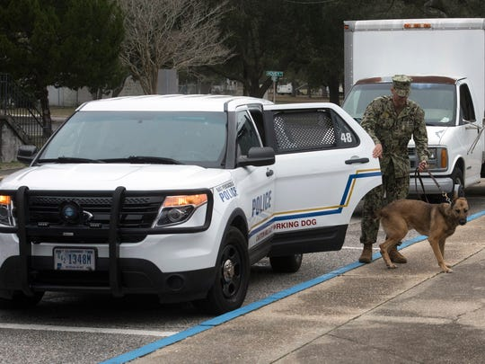 Petty Officer 1st Class Roberto Garcia and Heky, a military working dog, patrols the area around building 1500 on aboard Pensacola Naval Air Station Wednesday, Feb. 14, 2018.