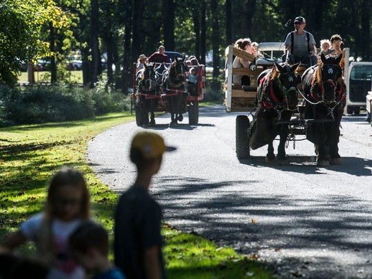 People wait in line for a horse-drawn hayride during the Harvest Festival at Wesselman Nature Society in Evansville, Ind.,, Saturday, Sept. 30, 2017. The festival, which ran from 2-8 p.m., offered guided hikes, nocturnal insect and animal encounters, live music around a bonfire and much more.