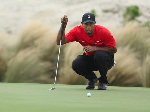 Woods of the United States lines up his putt on the