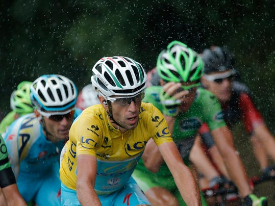 Italy's Vincenzo Nibali, wearing the overall leader's yellow jersey, rides in the rain during the nineteenth stage of the Tour de France cycling race over 208.5 kilometers (129.6 miles) with start in Maubourguet and finish in Bergerac, France, Friday, July 25, 2014. (AP Photo/Christophe Ena)