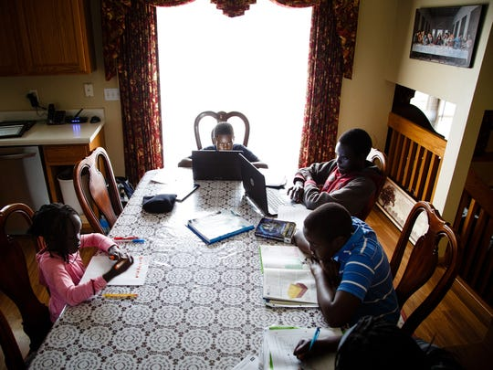 Five of the Akec family's six children including, Abeny, left, Anai, center, Bak, back right, Akec, center right, and Anyiel, bottom right, sit at the kitchen table and complete on their school work on Friday, March 10, 2017, in Des Moines. Every day all six children sit down for two hours to work on their homework together, says their mother Ayak Anaikur.