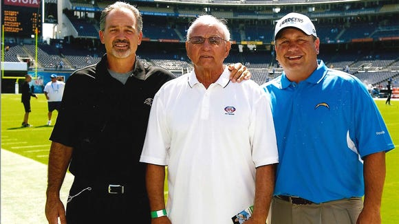 Chuck Pagano (left) with his father, Sam (middle), and brother John before a game when Chuck was defensive coordinator in Baltimore. Chuck, now head coach of the Colts, won his playoff game Saturday and John's Chargers defeated Cincinnati Sunday.