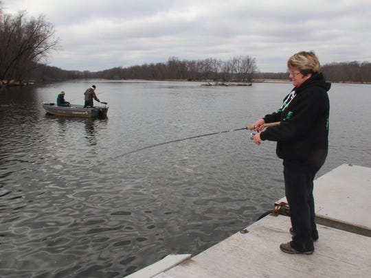 Nancy Roth of Manawa, Wis. fishes from the dock on the Wolf River at Red Banks Resort in Red Banks, Wis. as two anglers drift downstream in a boat. The spring walleye run draws thousands of anglers to the river each year.