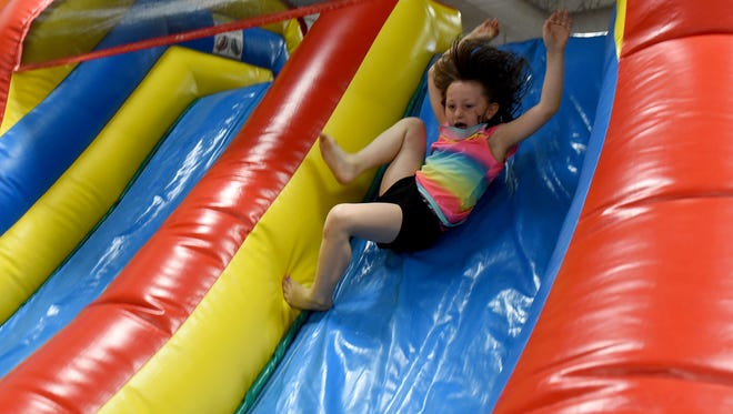 Ridgewood Elementary first grader Payge Kinney, 7, takes the slide out of an inflatable obstacle course during a celebration of the last day of school on Wednesday, May 23, 2018. Students enjoyed games, snacks, face painting, and a photo booth before the start of summer break.