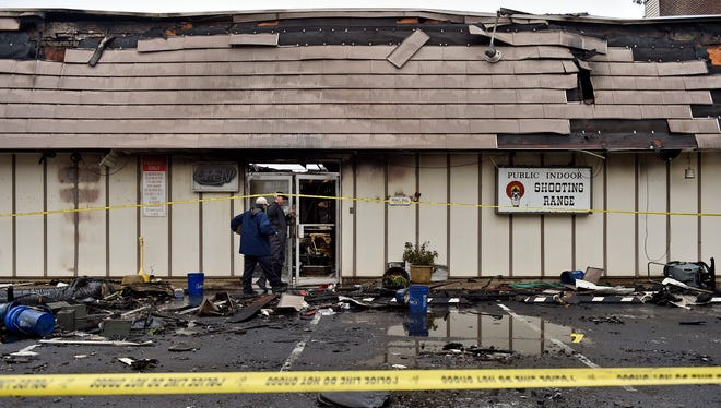 Law enforcement officers, including a fire marshal, enter the West York Sporting Goods store Saturday, the day after a three-alarm fire destroyed the indoor shooting range.