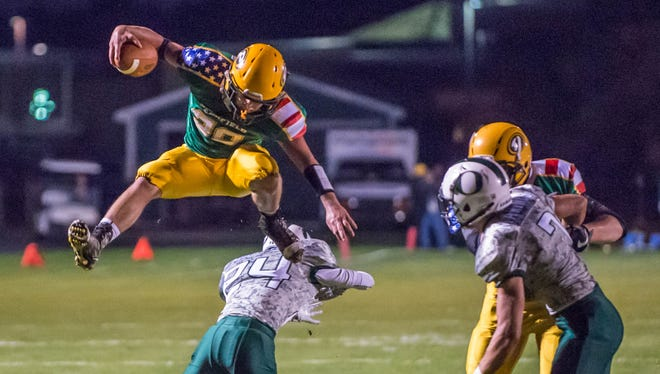Pennfield's Sam Nichols leaps over the Olivet defender during first half action Friday evening.