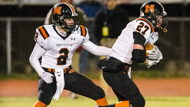 Northville quarterback Justin Zimbo hands off to P.J. Schneep in Friday's pre-district loss to Canton.