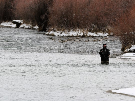 An angler casts his line in the San Juan River Monday afternoon at the Texas Hole as snow gathers on the banks. Conditions throughout the county varied as a winter storm blew through.