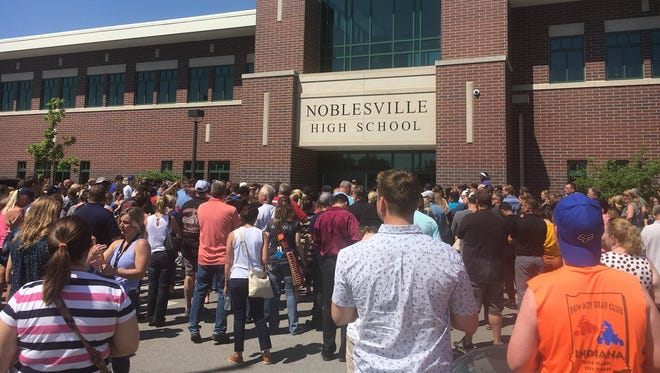 Students are starting to be released from the high school. Administrators are yelling names to the crowd of parents.
