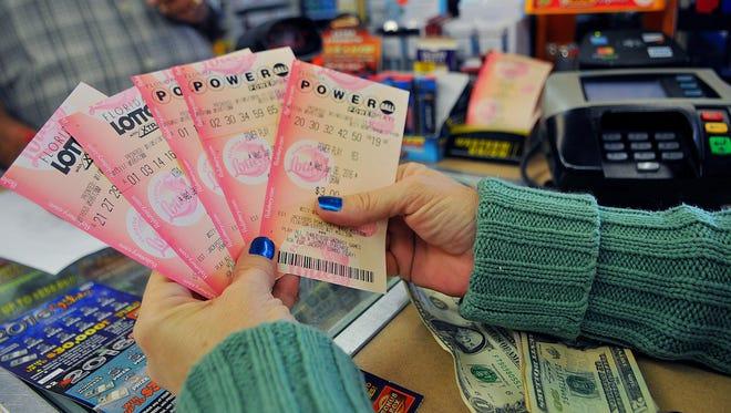 Johanne Eklund of Merritt Island buys her Powerball tickets for Wednesday night's $400 million dollar jackpot from Jim Patel, owner of the K & D Discount Beverage on Merritt Island.