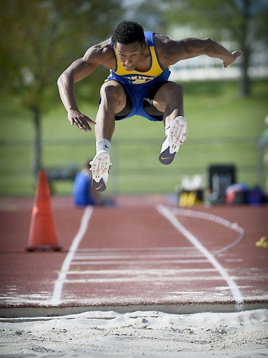 Dominic Trader launches himself into the air on the way to winning the triple jump.