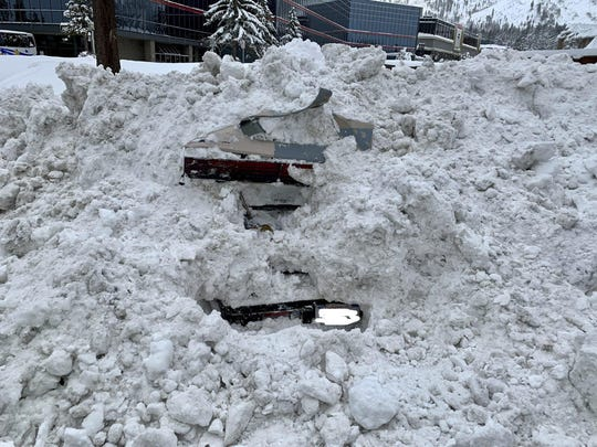 This Feb. 17, 2019 photo provided by City of South Lake Tahoe shows a car buried in snow in South Lake Tahoe, Calif. Authorities say a snowplow operator inadvertently bumped into a car buried in snow and found a woman unharmed inside.