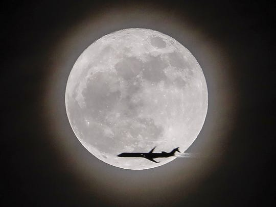 An airplane crosses in front of the moon, a so-called