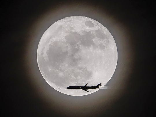 An airplane crosses in front of the moon, a so-called supermoon, in Avondale Estates, Georgia on Dec. 3, 2017.