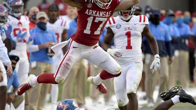 Arkansas defensive back Hudson Clark (17) leaps over Mississippi running back Tylan Knight (4) Saturday in Fayetteville, Ark.