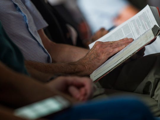 A congregant of Redemption City Church in Franklin holds onto his Bible during Sunday morning worship service June 4, 2017.