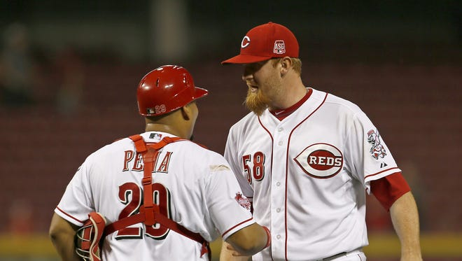 Cincinnati Reds catcher Brayan Pena (29) and relief pitcher Nate Adcock (58) celebrate at the mound following the last out of the game.